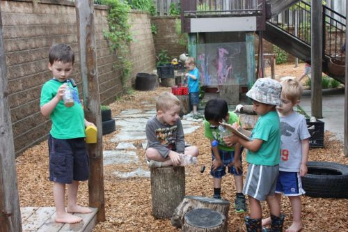 group of children playing outside with natural materials