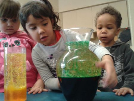 three children explore vases with different liquid contents and colours