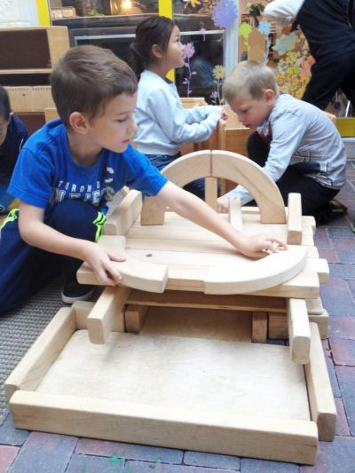 three school age children building using wooden blocks and materials