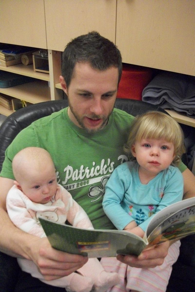 adult male reading to infant and toddler from book on his lap