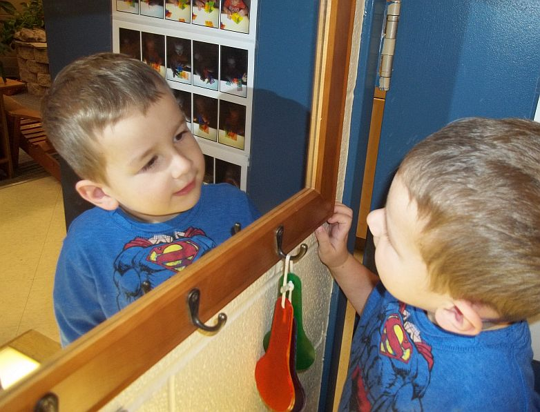 child looking at himself a the mirror and smiling