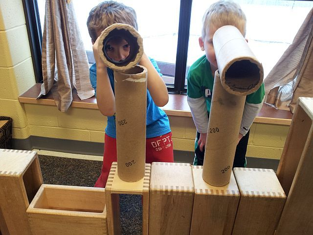 two children looking through two cylinders pretending that they are telescopes