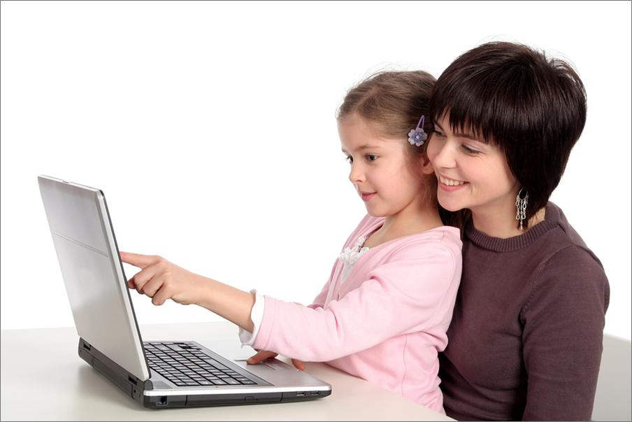 mother and daughter sit together looking at a laptop