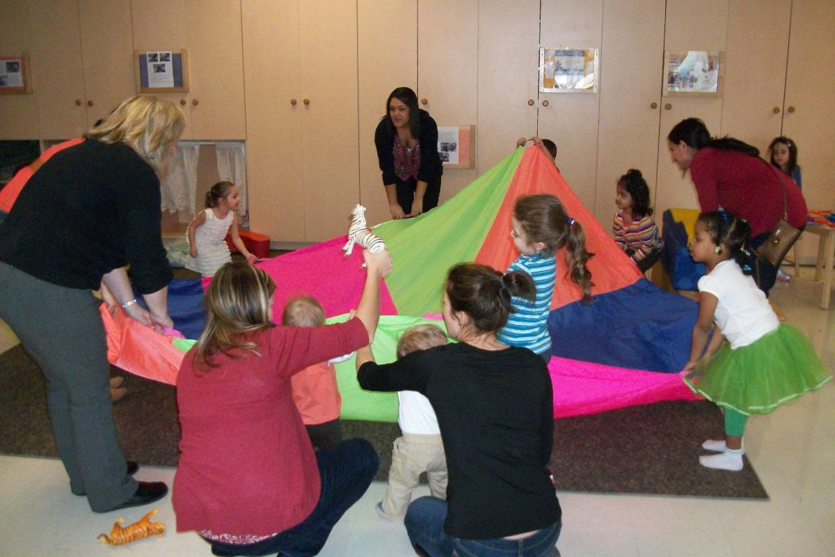 parents and children playing games in a group with large multi-coloured blanket