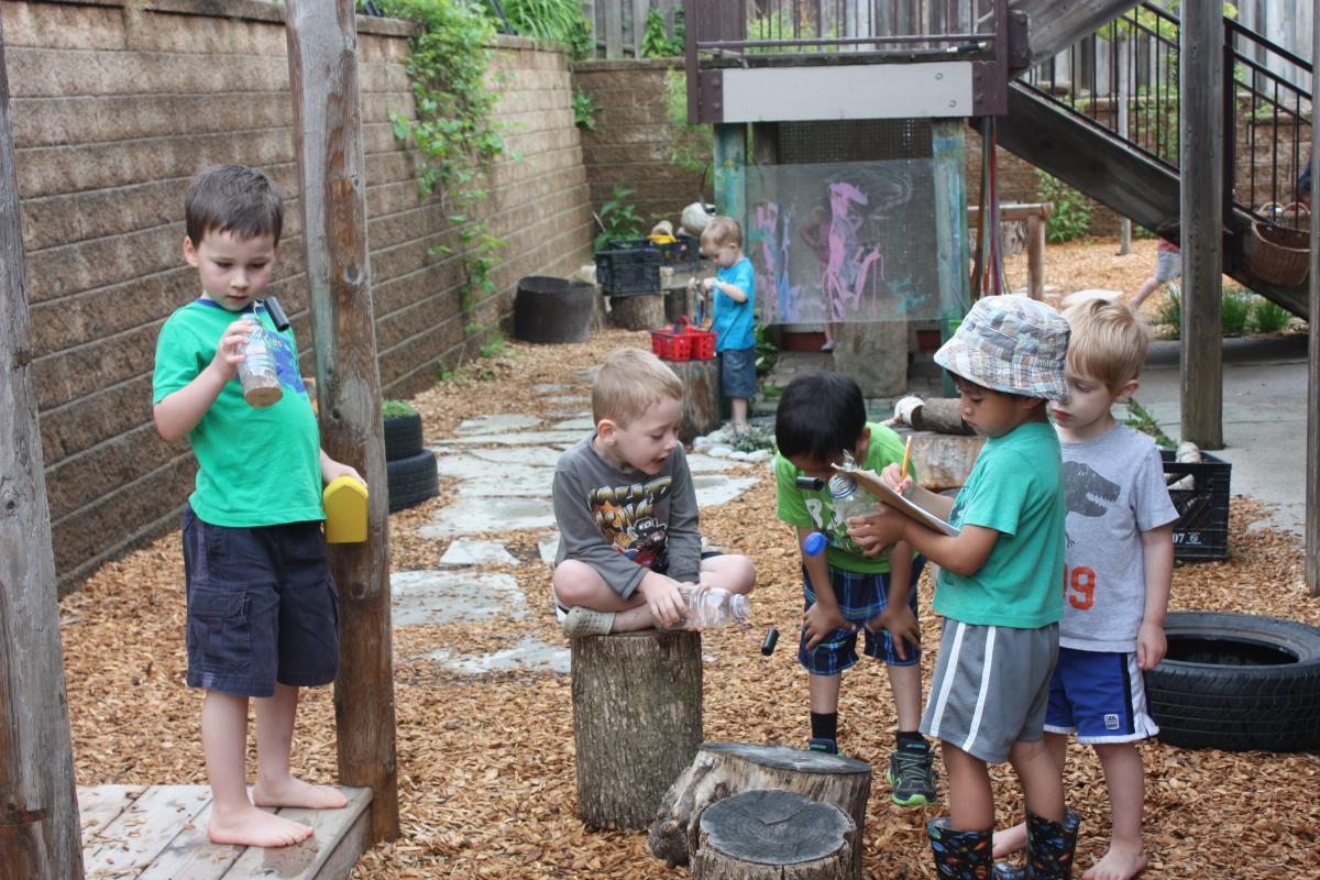 children playing outdoors with natural materials